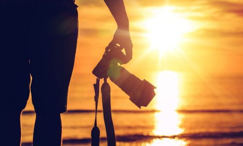 38013362 - sunset photography. photographer ready to take sunset pictures on the beach. professional travel photography works.