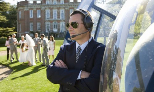 38090911 - helicopter pilot in sunglasses by helicopter, wedding party in background